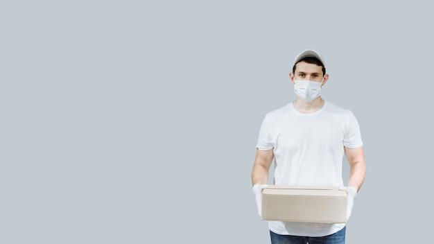 Il lavoratore dell'operaio di consegna a domicilio con maschera e guanti tiene la scatola di cartone vuota