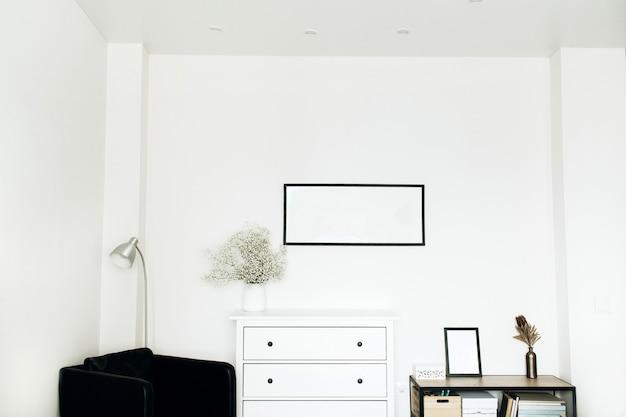 Interni di design per la casa con cornice per foto, bouquet di fiori bianchi e cassettiera, poltrona su sfondo bianco