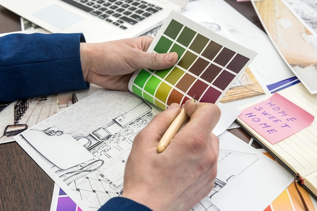 Il designer di casa lavora allo schizzo della casa dell'ufficio con il catalogo dei colori per un appartamento moderno da sogno pianta della casa di architettura e campione di colore, matita