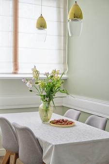 Interno sala da pranzo, bouquet di fiori primaverili, fragole