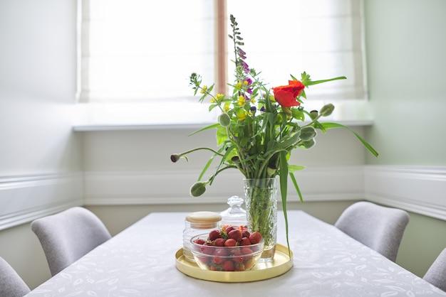 Interiore della sala da pranzo domestica, tavolo con tovaglia bianca, bouquet primaverile di fiori in vaso, vassoio con fragole mature