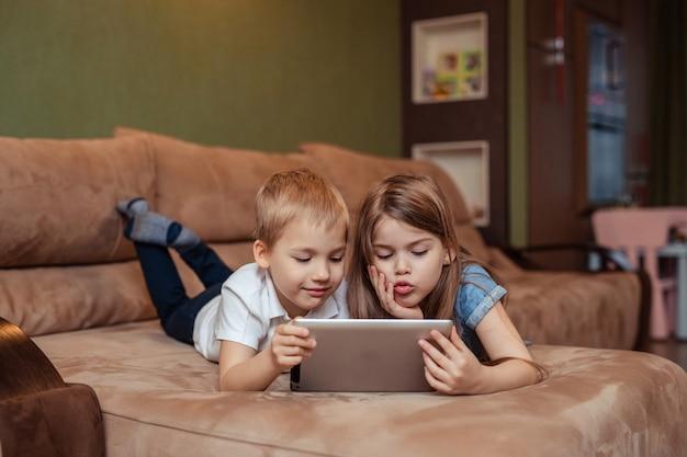 Apprendimento a distanza a casa a casa. gemelli fratello e sorella stanno studiando a casa usando un tablet. sono felici e ridono mentre giacciono sul divano