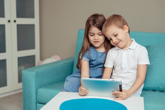 Apprendimento a distanza a casa a casa. gemelli fratello e sorella studiano a casa facendo uso della compressa