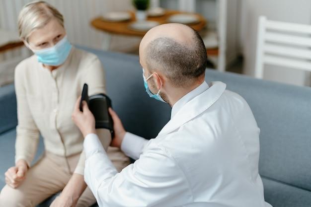 Il medico di casa sta misurando la pressione del suo paziente