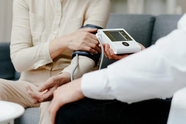 Medico domiciliare che misura la pressione sanguigna durante una visita al paziente