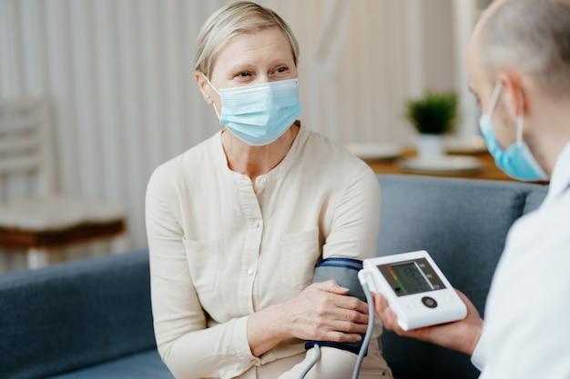 Medico di casa che mostra al paziente un misuratore di pressione sanguigna digitale