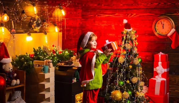 Casa piena di gioia e amore. buon natale e felice anno nuovo. auguri. vacanza in famiglia. regalo di natale. simpatico bambino gioca vicino all'albero di natale. il bambino si gode le vacanze invernali a casa.