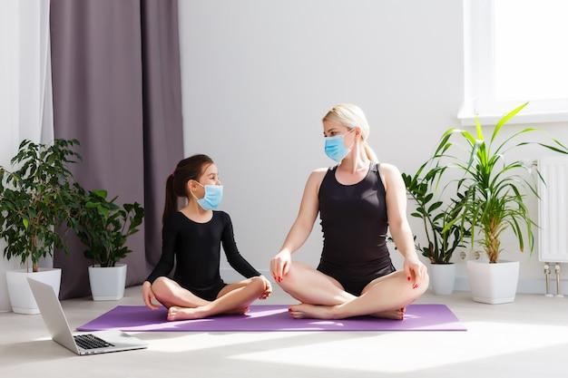 Fitness a casa. madre e figlia fanno yoga online a casa durante la quarantena di autoisolamento. il concetto covid-19 per promuovere la sicurezza a casa salva vite