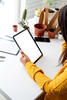 Giardinaggio domestico. mock up design. mani del giardiniere della donna che tengono compressa digitale con lo schermo in bianco