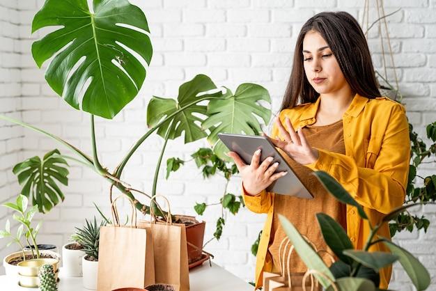 Giardinaggio domestico. piccola impresa. giardiniere della giovane donna che prende appunti nel blocco note, linea di borse per la spesa artigianali per impianto di confezionamento nella parte anteriore