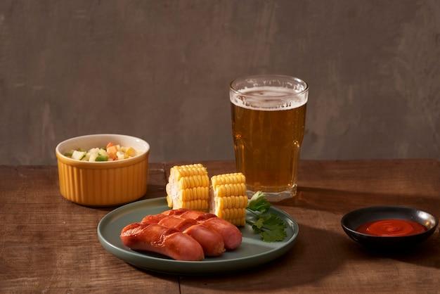 Salsicce grigliate in casa su un piatto scuro, un piatto di carne su un tavolo di legno scuro, salsicce calde con spezie e sale in una cucina di casa, copia spazio, stile rustico, arte