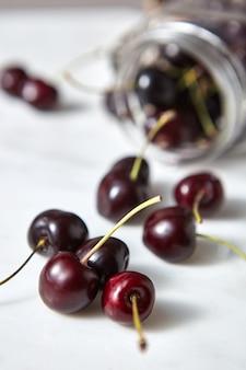 Ciliegie fresche naturali coltivate in casa con profondità di campo ridotta. ingredienti per la torta dolce ai frutti di bosco su bianco