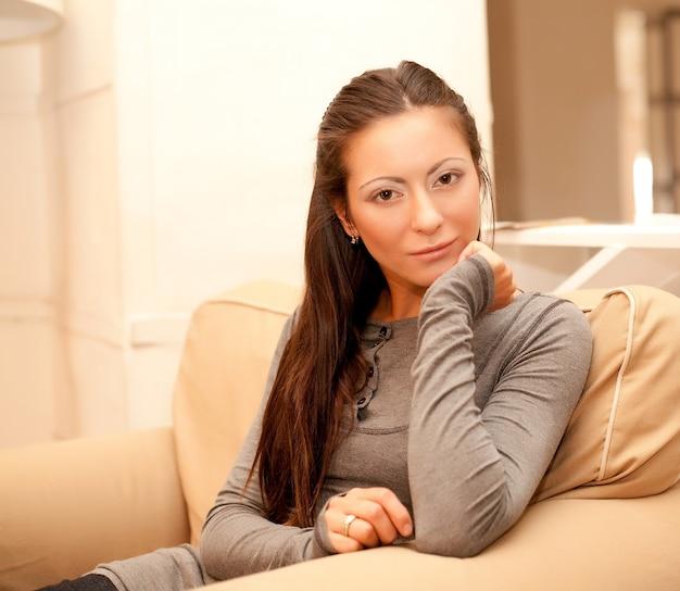 Casa e concetto di felicità - donna sorridente a casa