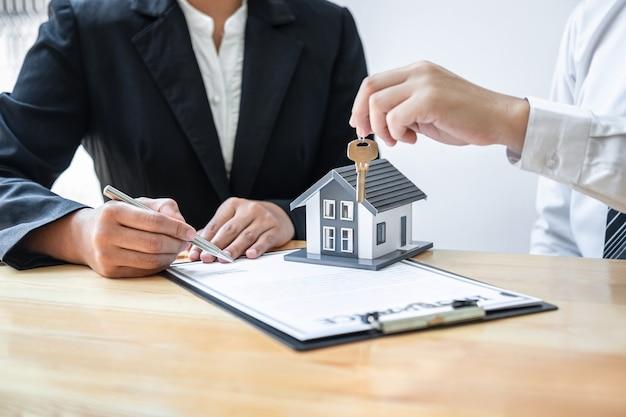 Assicurazione domestica e concetto di investimento immobiliare, agente di vendita che fornisce la chiave della casa al nuovo cliente dopo aver firmato il contratto di accordo con il modulo di domanda di proprietà approvato.