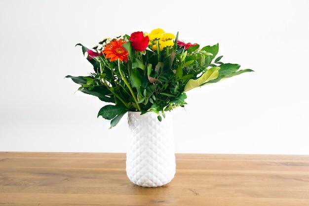 Decorazione di interni per la casa bouquet colorfol in un vaso bianco e parete bianca su un tavolo in legno mod...