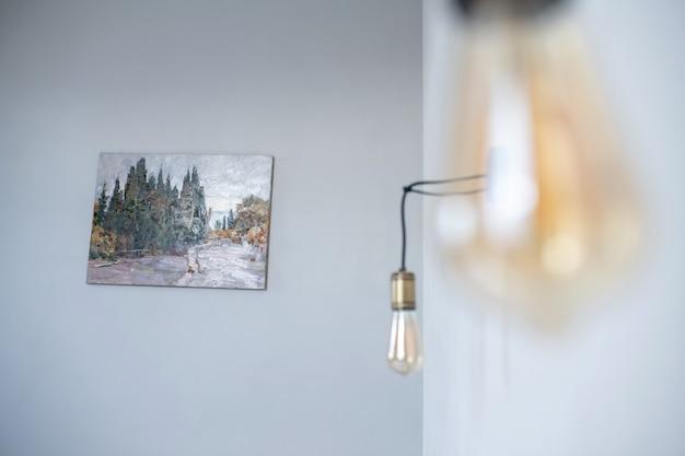 Lampada domestica. piccola lampada appesa al muro bianco e natura morta nella stanza con la luce del giorno