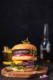 Hamburger fatto in casa con due cotolette e formaggio fuso, birra su un tavolo con spazio per le copie