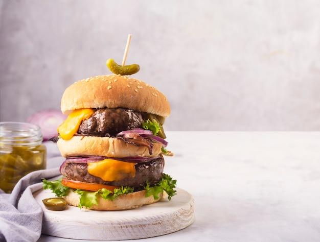 Hamburger fatto in casa con due cotolette e formaggio fuso con cipolla e pancetta su uno sfondo grigio cemento con spazio copia