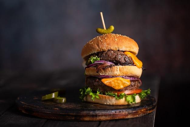 Hamburger fatto in casa con due cotolette e formaggio fuso con cipolla e pancetta su tavola di legno con spazio copia