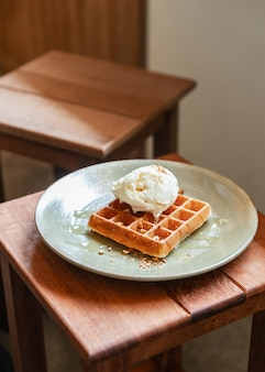 Waffle classico fatto in casa topping con una pallina di gelato alla vaniglia. topping con mandorle tritate e sciroppo d'acero. servito in un piatto di ceramica.