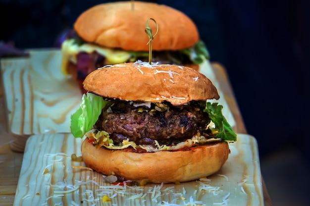 Hamburger fatto in casa con lattuga, formaggio, carne di manzo e patatine fritte disposte su un vecchio tavolo di legno. due grandi hamburger gustosi con patty spessi e verdure con panini tostati. cibo fatto in casa.