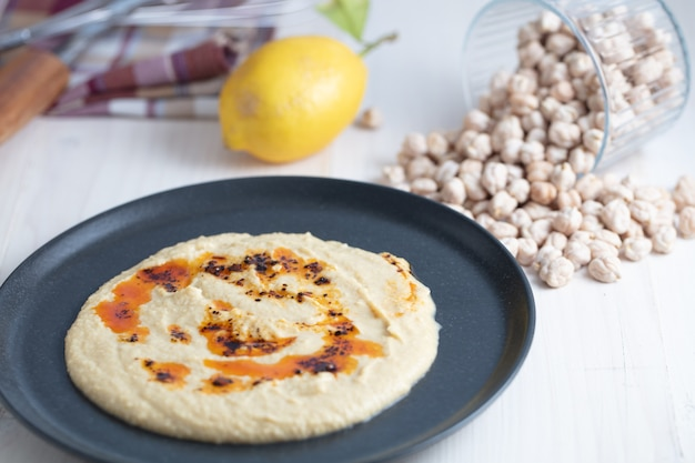 Ciotola per hummus fatta in casa, decorata con ceci bolliti, limone e olio d'oliva su uno sfondo bianco rustico.