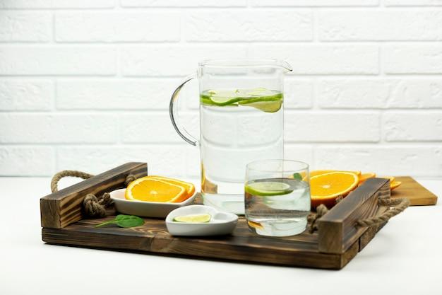 Una limonata fatta in casa a base di lime si trova in un bicchiere e una brocca su un vassoio di legno con arance intorno