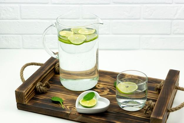 Una limonata fatta in casa a base di calce si trova in un bicchiere e una brocca su un vassoio di legno