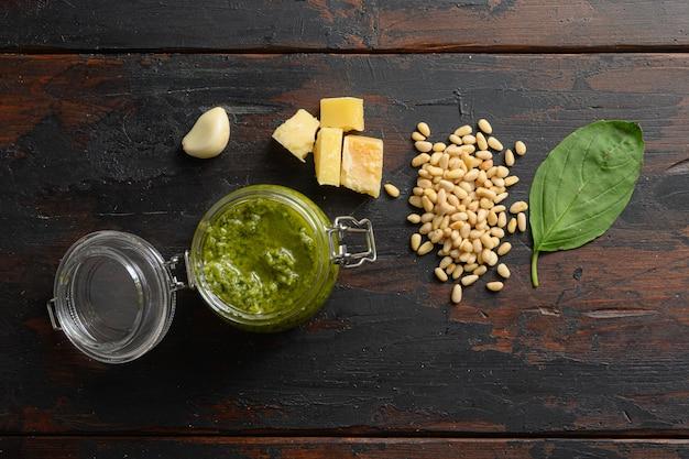Pesto fatto in casa in barattolo di vetro con ingredienti parmigiano basilico pinoli. su tavola di legno scuro vista dall'alto vintage.