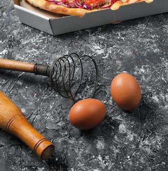 Pizza fatta in casa, uova, corolla su fondo rustico grigio