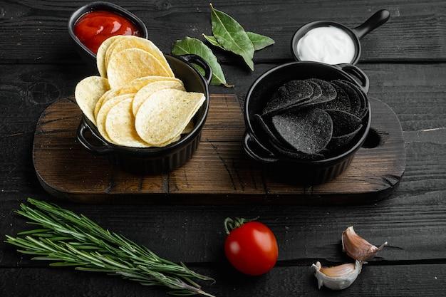 Set di patatine fatte in casa, su fondo di legno nero