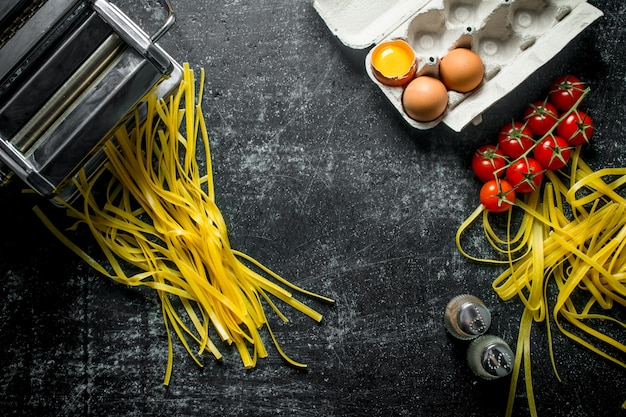 Pasta cruda fatta in casa con pomodori su un ramo, uova e spezie. sul nero rustico