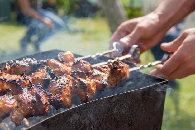 Shaslik fatto in casa sul fuoco aperto gli shish kebab stanno friggendo sulla griglia del barbecue Foto Premium