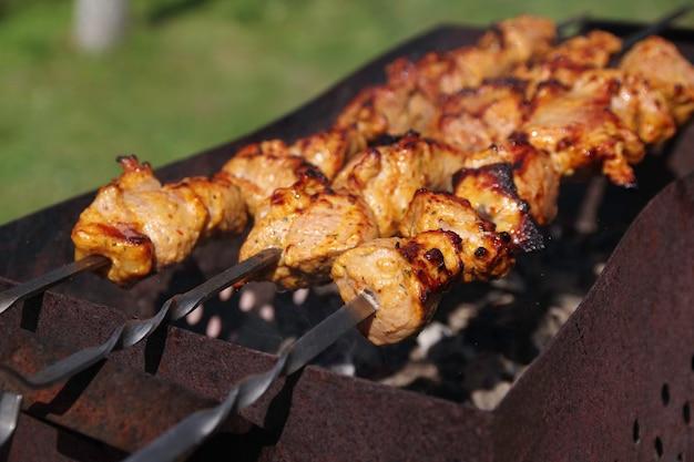 Shaslik fatto in casa sul fuoco aperto gli shish kebab stanno friggendo sulla griglia del barbecue