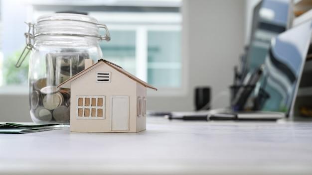 Modello domestico e barattoli di vetro con monete che mettono sul tavolo bianco. pianificazione del risparmio di denaro per acquistare una casa o un concetto di investimento immobiliare.