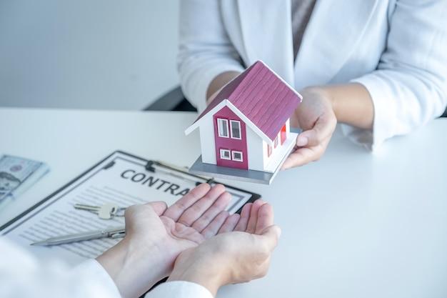 Modello di casa nelle mani, l'agente immobiliare spiega all'acquirente il contratto di lavoro, l'affitto, l'acquisto, il mutuo, il prestito o l'assicurazione sulla casa.