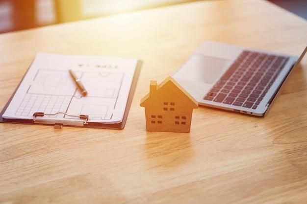 Modello di casa messo vicino a documento di contratto di locazione o di noleggio e laptop con spazio di copia, attività immobiliare per l'acquisto, il prestito o il concetto di investimento