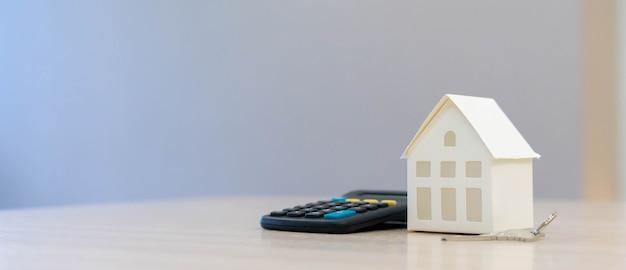 Modello di casa con calcolatrice o gestione del denaro, concetto finanziario di mutuo per la casa
