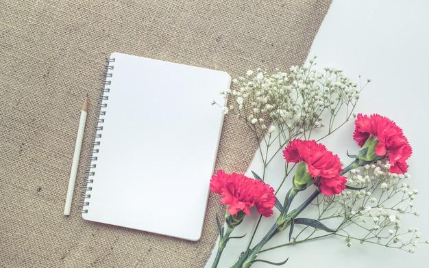 Tavolo scrivania da ufficio con blocco note, bouquet di fiori su sfondo di tela di sacco.