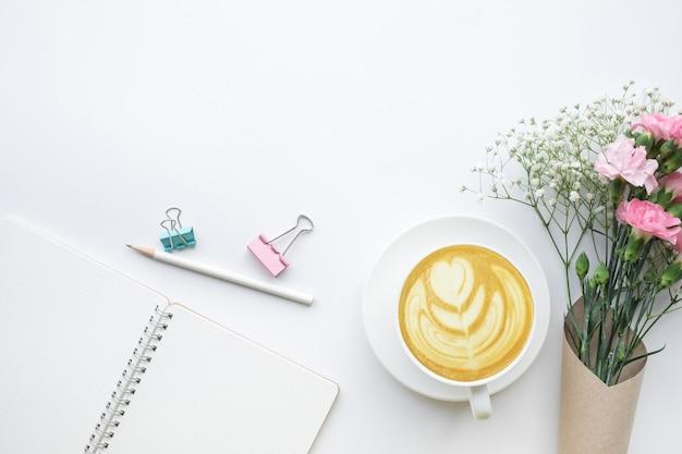 Tavolo scrivania da casa con blocco note, bouquet di fiori su sfondo bianco