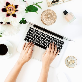 Area di lavoro del tavolo scrivania da casa con computer portatile e fiori su superficie bianca