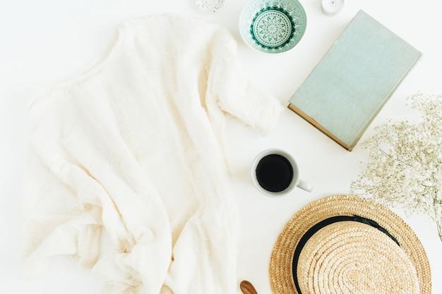 Scrivania da ufficio con caffè, libro, cappello di paglia e coperta su superficie bianca