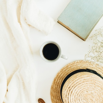 Scrivania da ufficio con caffè, libro, cappello di paglia, fiori e coperta su superficie bianca
