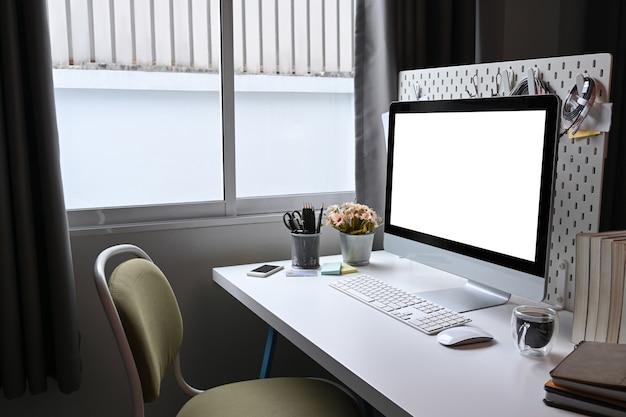 Scrivania da casa con computer, tazza di caffè e libri sulla scrivania bianca.