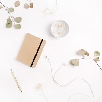 Scrivania da ufficio con diario artigianale, penna, cuffie e rami di eucalipto su sfondo bianco. disposizione piatta, vista dall'alto