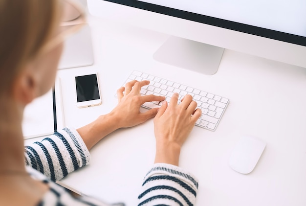 Scrivania da casa. spazio di lavoro delle donne. mani femminili che digitano testo sulla tastiera del computer. vista dall'alto, modello.