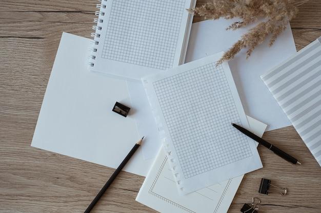 Area di lavoro della scrivania dell'ufficio domestico con fogli di carta bianca, quaderno, erba della pampa