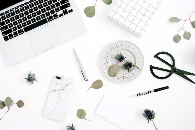 Area di lavoro della scrivania dell'ufficio domestico con laptop, telefono cellulare con custodia in marmo, penna, carta, taccuino e rami di eucalipto su sfondo bianco