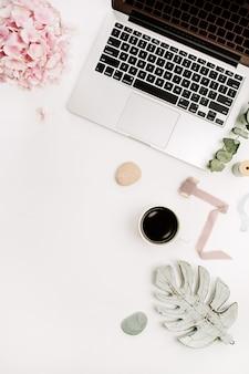 Area di lavoro scrivania da casa con laptop, fiori di ortensie rosa e accessori su sfondo bianco. vista piana laico e dall'alto.