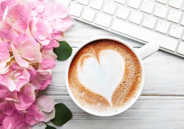 Area di lavoro scrivania da casa con bouquet di fiori di ortensie rosa, tazza di caffè e tastiera su fondo di legno bianco. flatlay, vista dall'alto.